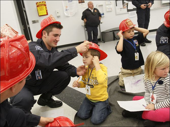 Penta student Tyler Rozek, 17, of Genoa, center left, helps Chase Cook, 4, of Perrysburg, put on his helmet during a fire safety training session Wednesday put on for the children by Penta's Public Safety/EMT-Fire Science program.