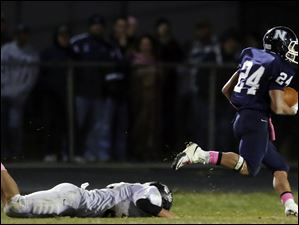 Napoleon HB Charlie Harris (24) runs past Perrysburg DB Trenton Demmerling (27) to score a touchdown.