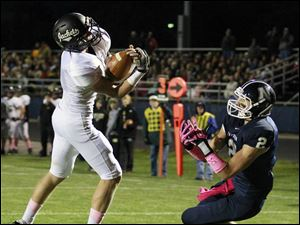 Perrysburg QB Steve Slocum (1) intercepts a pass intended for Napoleon WR Jordan Lauf (2) in the endzone.