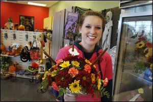 Floral Design and Greenhouse Production program student Abby Lutes, 17, of Walbridge, holds an arrangement she created for Thursday's Fall Harvest Sale at Penta Career Center in Perrysburg Township.