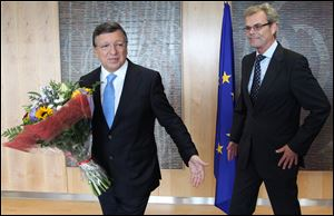 European Commission President Jose Manuel Barroso, left, receives flowers by Norway's ambassador to the EU Atle Leikvoll, after the 2012 Nobel Peace Prize was given to the EU, at the European Commission headquarters in Brussels on Friday.