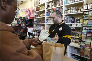Marvin Kiezi sells scratch-off lottery tickets Thursday at Navarre Carryout in Oregon, Ohio.