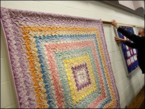 Tedd Long, a member of Sylvania First United Methodist, hangs a quilt.