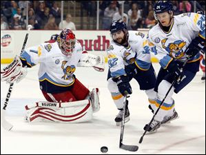 Toledo Walleye goalie Petr Mrazek (1), Cody Lampl (32), and Byron Froese (24) defend the net.