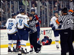 Toledo Walleye's Phil Oreskovic (4) is held back by an official after clocking Kalamazoo's Eric Kattelus (15) during the second  period.