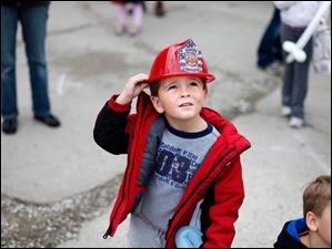 Caleb Jones, 5, watches as a fire truck ladder is lowered.
