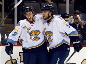 Toledo Walleye Max Campbell (19) celebrates with Phil Oreskovic (4) after scoring a goal against Kalamazoo.