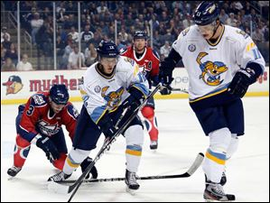 Toledo Walleye's Travis Novak (12) and Andrej Nestrasil (11) move the puck.