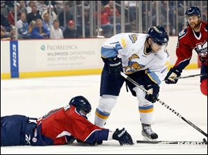 Toledo Walleye's Joey Martin (14)  moves the puck against  Kalamazoo's Adam Polasek (3).
