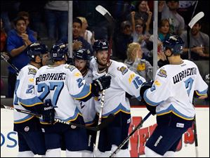 Toledo Walleye's Willie Coetzee (15), center, celebrates his goal score with teammates Byron Froese (24), Terry Broadhurst (27), Joey Ryan (16), and Dale Warkentin (3).
