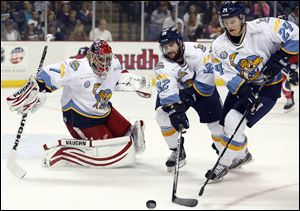 Toledo Walleye goalie Petr Mrazek (1), Cody Lampl (32), and Byron Froese (24) defend the net against Kalamazoo.