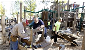 Volunteers Steve Roth, left, and Brock Cahill help build Imagination Kingdom, a $250,000 playground on the south side of Reighard Park in Wauseon.