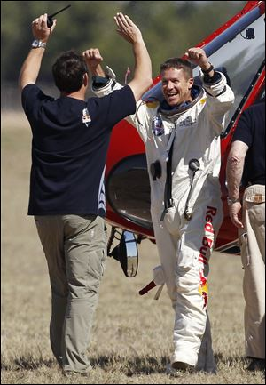 Felix Baumgartner, right, of Austria, celebrates with Luke Aikins, team skydiving consultant, after Baumgartner successfully jumped from a space capsule lifted by a helium balloon at a height of just over 128,000 feet above the Earth's surface, Sunday,  in Roswell, N.M.