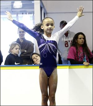Halle Faulkner, 8, from Westland, Mich., ends her bar routine on the mat with a grin for the judges during a gymnastics meet..
