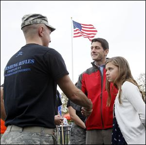 GOP vice-presidential nominee Paul Ryan, center, and his daughter  Elizabeth Ryan, 10, right, greet a member of the BGSU Pershing Rifles Company I-1 before the BGSU football game Saturday at Doyt L. Perry Stadium.