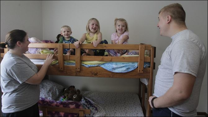Hope, left, and Brandon Fritz, right, watch their three children Hope, left, and Brandon Fritz, right, watch their three children -- Noah, 2, Makenzie, 6, and Bralynn, 3 -- sit on the bunk beds the girls received from First Presbyterian Church in Monroe. The church has a program to help families who cannot afford children's beds.