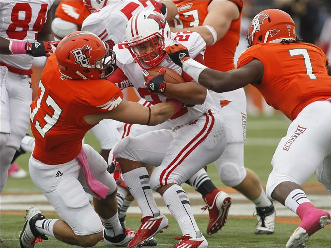 Bowling Green's Paul Swan, 33, and D.J. Lynch, 7, stop Miami's Spencer Treadwell at the line of scrimmage.