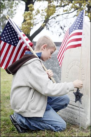 Maston Jaquillard, 11, a sixth grader at Navarre Elementary, puts flags on graves of Civil War Veterans during the annual cemetery walk. He said it was an 'honor to do it.'