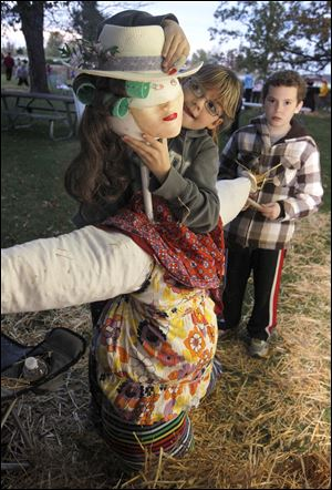 Cygnet, Ohio residents Bella Byram, 8, and Bryan Byram, 11, build a scarecrow.