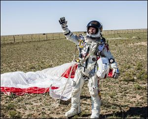 In this photo provided by Red Bull Stratos, Pilot Felix Baumgartner of Austria celebrates after successfully completing the final manned flight for Red Bull Stratos in Roswell, N.M., Sunday. Baumgartner came down safely in the eastern New Mexico desert minutes about nine minutes after jumping from his capsule 128,097 feet, or roughly 24 miles, above Earth.