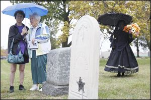 Dori Wolf, left, and Lois Helm-Webb, related to the Haughton family, listen to speakers. One of Ms. Helm-Webb's ancestors, Ira Haughton, is among the Civil War veterans buried there.
