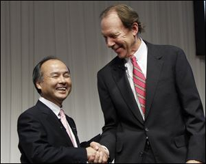 Softbank Corp. President Masayoshi Son, left, and Sprint Nextel Corp. Chief Executive Dan Hesse shake hands during their joint press conference in Tokyo.