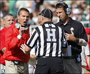 Ohio State Buckeyes head coach Urban Meyer and Luke Fickell yell at a referee during the 1st quarter against Michigan State Spartans in the NCAA college football game at Spartan Stadium in East Lansing, Michigan on Sept. 29.