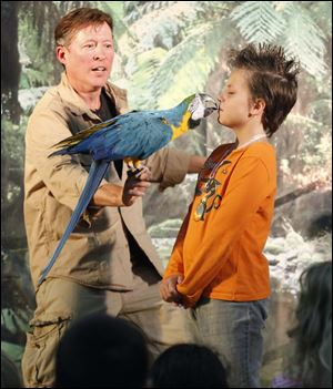 Animal handler Mike Kohlrieser prompts a bird to kiss Starr Elementary student Rhianna Blossom, 10, during a Rain Forest show at Coy Elementary School in Oregon.