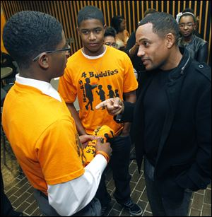 Rogers High School student Brandon Jackson, left, and Southview's Dannie Duhart speak with CSI: NY actor and author Hill Harper.