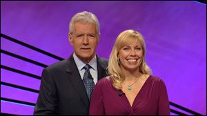 Jeopardy host Alex Trebek stands next to Stephanie Jass after she won more than $147,000 on the quiz show. Jass is an associate professor from Michigan.
