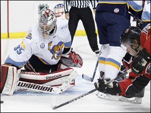 Walleye goalie Kent Simpson, 35, blocks a shot by a diving Nathan Moon, 19, of the Cincinnati Cyclones.