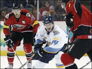 Walleye player Joey Martin,14, takes the puck against Cincinnati Cyclones player Maury Edwards, 6.