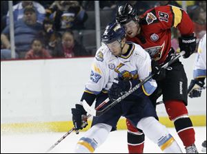 Walleye player Luke Glendening, 23, battles for the puck with Cincinnati Cyclones player Nathan Moon, 19.