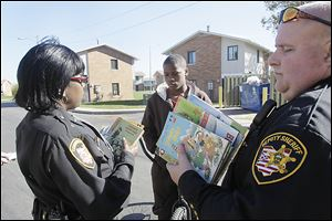 Ella P. Stewart Academy for Girls students inspect books brought by Lucas County sheriff's deputies in the Books 4 Buddies program.