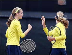 Notre Dame Academy sophmore Teagan McNamara, left, celebrates a point as doubles partner Alicia Nahhas watches the shot land just out of bounds.