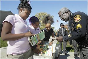 Ella P. Stewart Academy for Girls sixth graders Najae Pettaway, left, Taylor Hughes, and Jayona Wren search through some of the books brought to the school by Lucas County sheriff's Deputies E.L. Linzy, right, and Valerie Hughley, background.