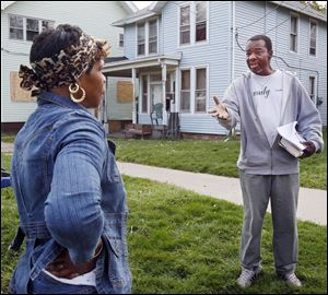 Deacon Zettie Williams, right, tries to encourage a Mayville Place resident to join a neighborhood group Thursday.