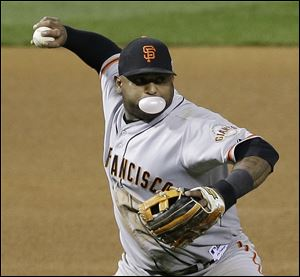 San Francisco Giants third baseman Pablo Sandoval blows a bubble as he fields a ball hit by St. Louis Cardinals' Jon Jay during the fifth inning Friday in St. Louis.