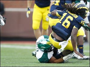 Michigan quarterback Denard Robinson, 16, loses his shoe before being tackled by Michigan State's Denicos Allen, 28.