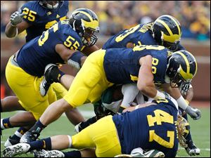 Michigan State's Tony Lippett is crushed by Michigan defenders Kenny Demens, 25, Jibreel Black, 55, Thomas Gordon, 30, Craig Roh, 88, and Jake Ryan, 47.