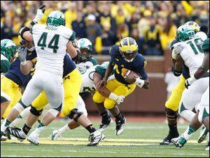 Michigan quarterback Denard Robinson, 16, is tackled for a loss by Michigan State University player Denicos Allen, 28.