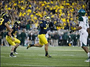 Michigan place kicker Brendan Gibbons reacts after kicking the game winning field goal to beat Michigan State University 12-10 at Michigan Stadium in Ann Arbor.