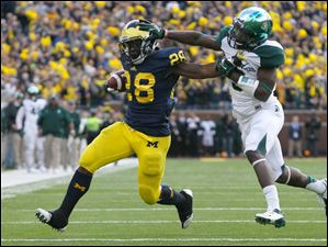UM's Fitzgerald Toussaint is tackled by Michigan State University player Isaiah Lewis.