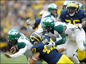 Michigan player Jake Ryan, 47, sacks Michigan State quarterback Andrew Maxwell as MSU's Le'Veon Bell, 24, and Michigan's Quinton Washington, 76, are also in on the play.