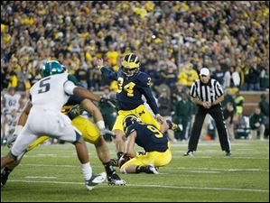 Michigan place kicker Brendan Gibbons kicks the game-winning field goal to beat Michigan State.