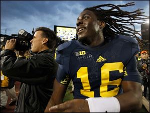 Michigan quarterback Denard Robinson bounces off the field after the Wolverines defeat Michigan State.
