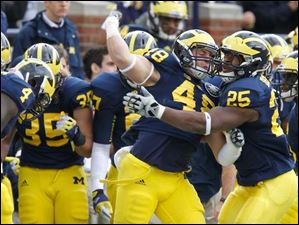 Michigan players Desmond Morgan, 48, and Kenny Demens, 25, celebrate after Morgan tackles Michigan State's Aaron Burbridge, 16, short of the first down on third down.