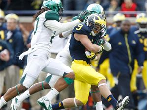 Michigan's Drew Dileo, 9, picks up a first down before being tackled by Michigan State's Kurtis Drummond, 27, and Darqueze Dennard, 31.