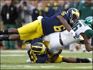Michigan players Raymon Taylor, 6, and Thomas Gordon, 30, tackle Michigan State University player Aaron Burbridge.