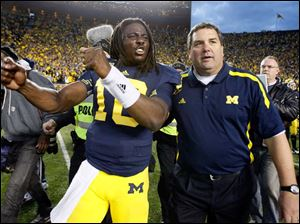Michigan quarterback Denard Robinson and head coach Brady Hoke celebrate.